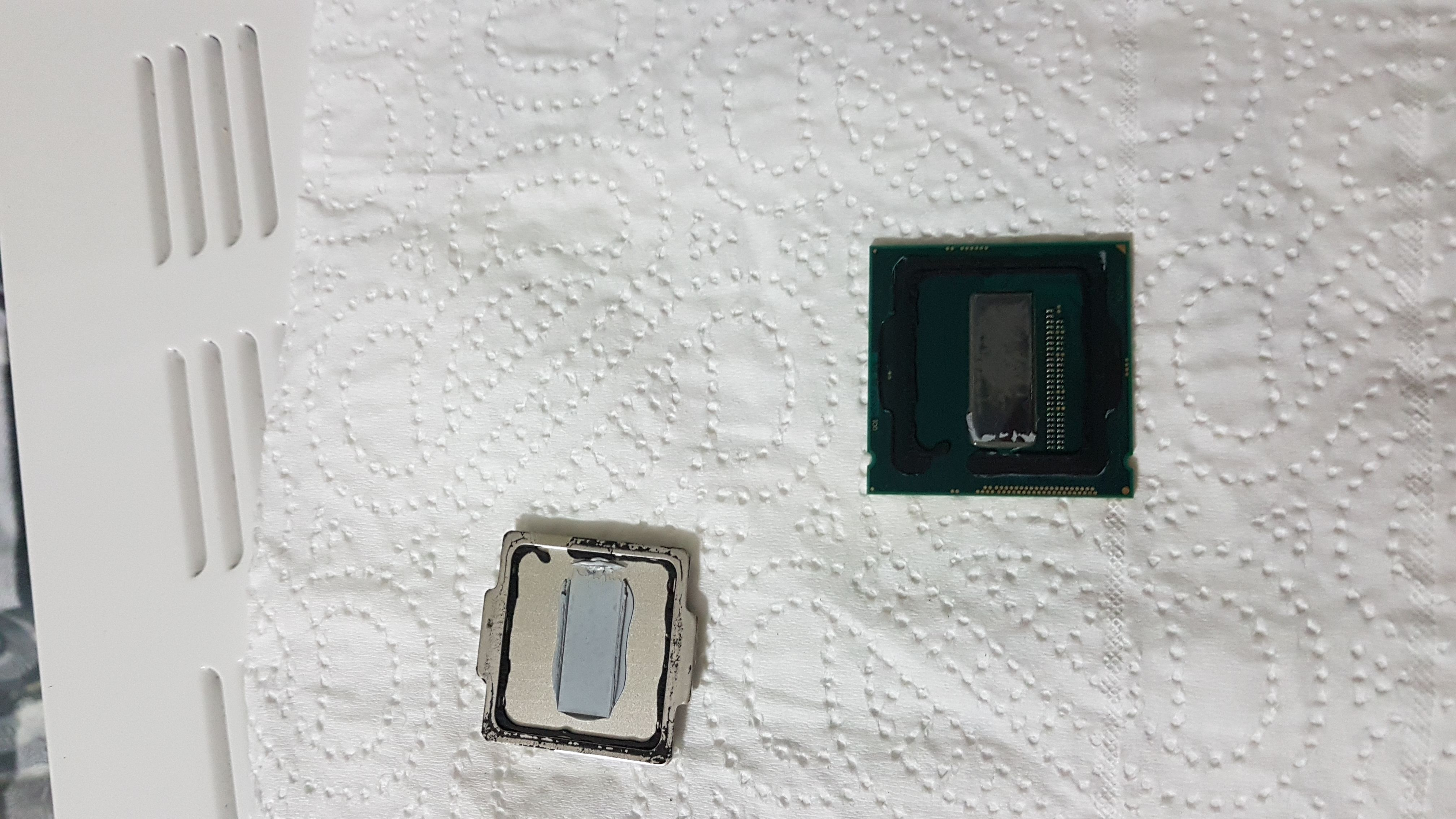 La CPU appena scoperchiata e piena di residui di pasta termica e silicone
